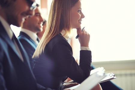 Rij van mensen uit het bedrijfsleven maken van aantekeningen tijdens seminar, gericht op attente jonge vrouwelijke