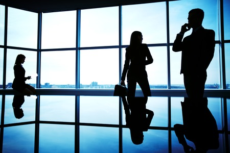 Silhouettes of several office workers working in office photo