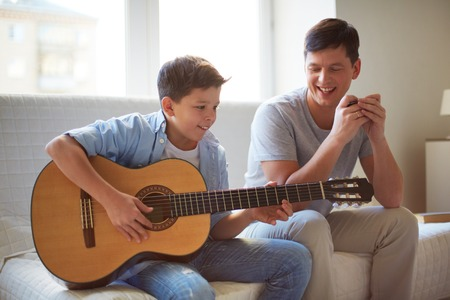Portrait of handsome young man teaching his son how to play the guitar photo
