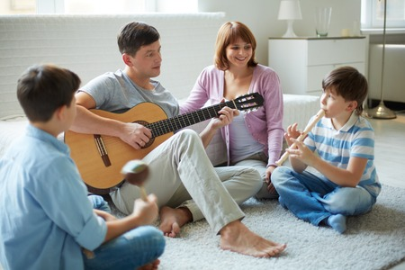 Woman beat guitar: Portrait of handsome siblings and their father playing musical instruments at home