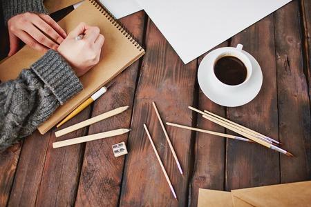 Foto van een kopje koffie en objecten voor de hand tekenen en mannelijke handen over notepad