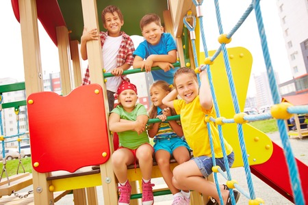 Image of joyful friends having fun on playground outdoors  photo
