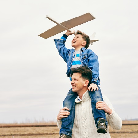 offspring: Photo of happy boy with toy airplane and his father playing together outside Stock Photo
