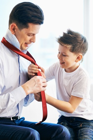 Photo of happy boy looking at his father tying necktie photo