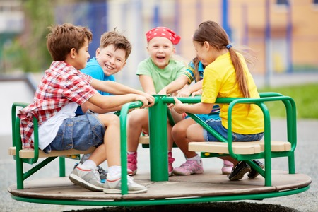 playground ride: Image of joyful friends having fun on carousel outdoors  Stock Photo