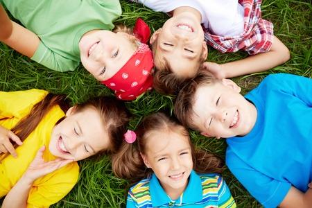 Group of cute children lying on green grass