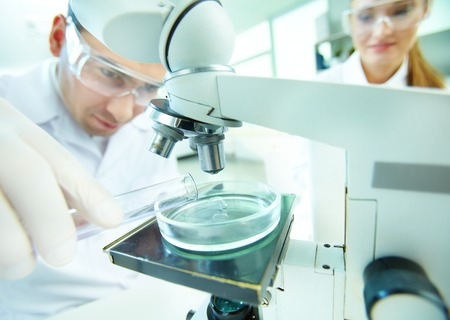 Male clinician studying chemical element in laboratory with his assistant near by Stock Photo - 27697312
