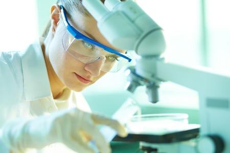 biochemist: Female biochemist mixing substances to study under the microscope