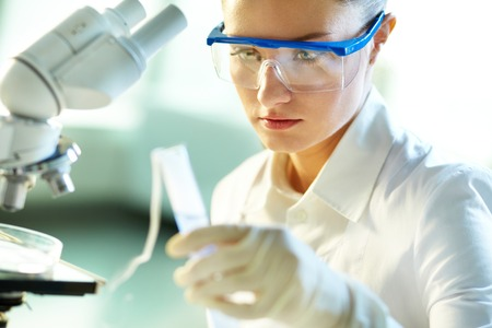 Female biochemist researching new substances in chemical lab Stock Photo - 27697349