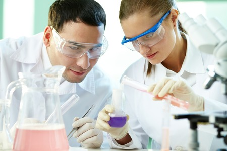 Portrait of two chemists working with different liquids in tubes photo