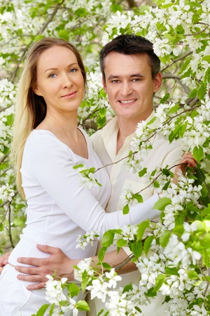 Portrait of young couple looking at camera between blooming apple-trees Stock Photo - 27697459