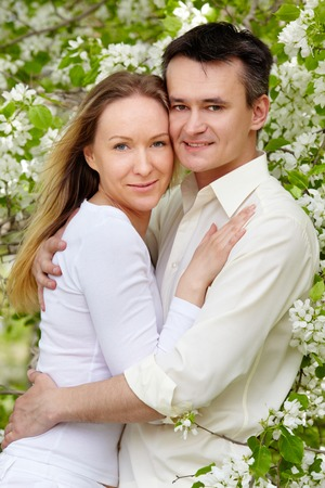 Portrait of young couple embracing and looking at camera in park Stock Photo - 27697460