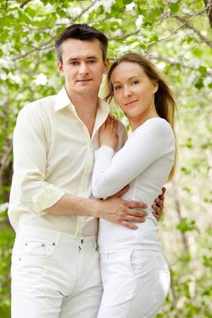 Portrait of young amorous couple looking at camera in park Stock Photo - 27697462