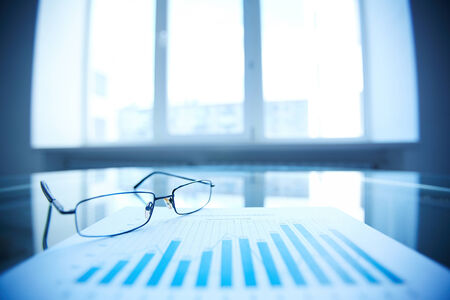 Image of eyeglasses and document on workplace Stock Photo