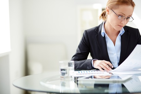 mujeres: Joven empresaria sentado en el lugar de trabajo y lectura de papel en la oficina