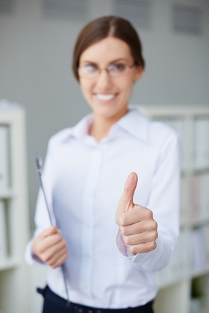 Young businesswoman showing thumb up photo