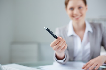 hand pen: Young businesswoman giving pen to somebody