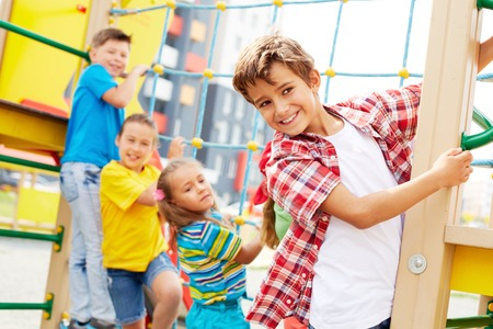 Image of cute kids having fun on playground outdoors, focus on smiling boy Stock Photo