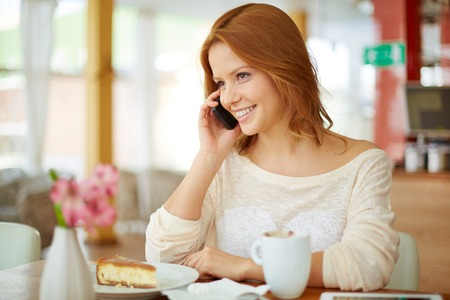 Image of young female speaking on the phone in cafe Stock Photo