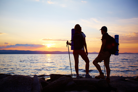 Rear view of couple of hikers standing by water in the evening photo