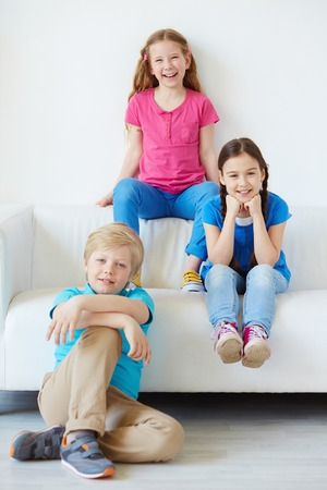 brothers and sisters: Three little friends looking at camera with smiles  Stock Photo