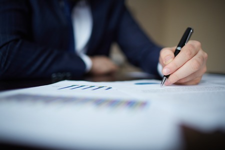 Image of human hand with pen over documents at workplace photo