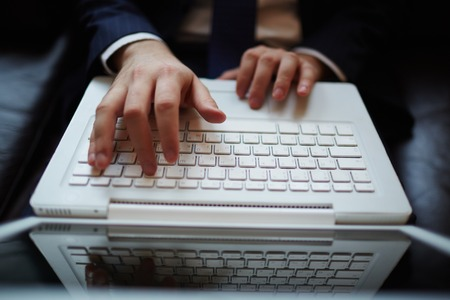 Male hands typing on laptop photo