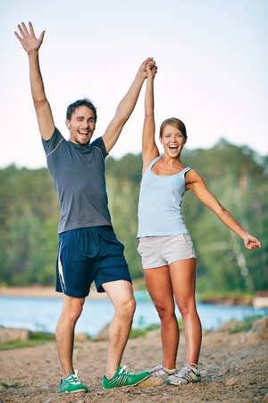 Photo of happy couple raising arms outdoors photo