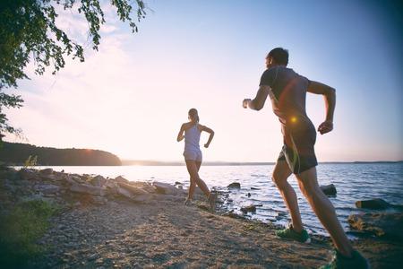 hombres corriendo: Vista trasera de la joven pareja que se ejecuta en la costa
