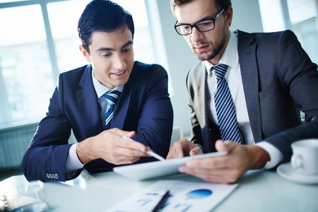 gadget: Image of two young businessmen discussing document in touchpad at meeting Stock Photo