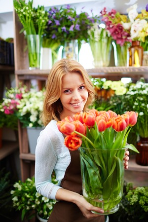 Portrait of young female florist with big vase of red tulips looking at camera photo