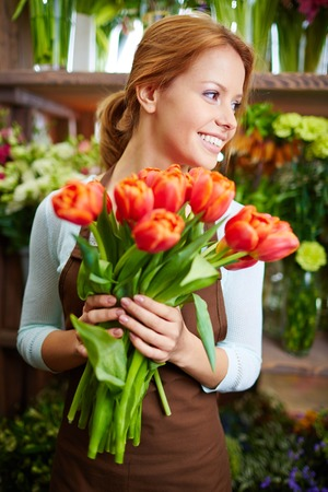 Portrait of young female florist with red tulips photo