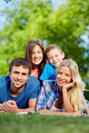 youngsters: Photo of happy family of four relaxing on grass during summer rest Stock Photo