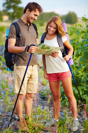 Portrait of young hikers looking at map in the countryside at summer photo