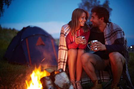 Young couple sitting by the fire and drinking tea outside photo