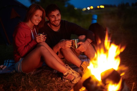 Young couple sitting on the ground and drinking tea while looking at fire
