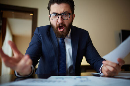 persona enojada: Hombre de negocios enojado con el documento gritando a alguien