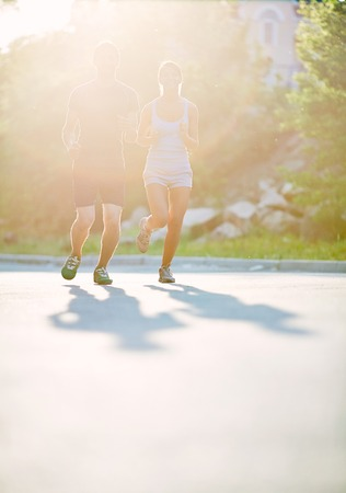 Photo of young couple running on sunny morning outdoors photo