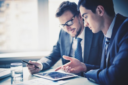 touchpad: Image of two young businessmen using touchpad at meeting Stock Photo