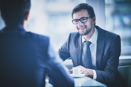 business interview: Image of young businessman having talk with his colleague Stock Photo