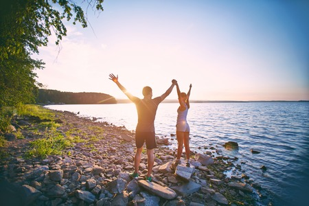 Photo of young sporty couple standing on the coastline with raised arms