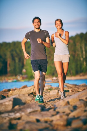 Photo of happy couple running outdoors Stock Photo