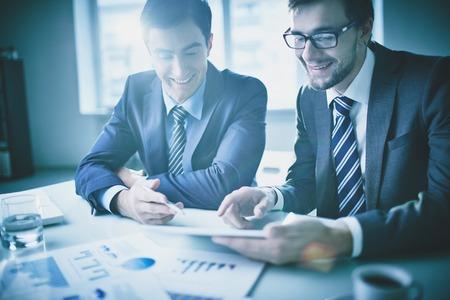 Obrázek dvou mladých podnikatelů diskutovat dokument touchpad na zasedání