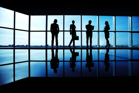 Silhouettes of several office workers standing on background of window photo
