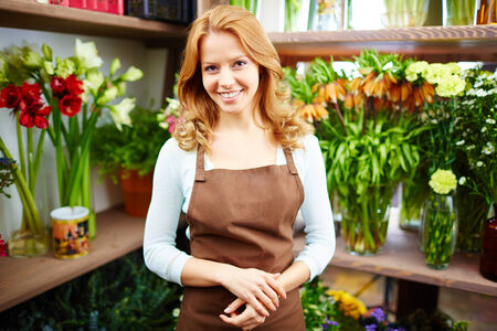 Portrait of happy young female florist looking at camera in floral shop photo