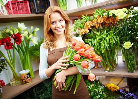 カメラ目線の赤いチューリップの束と幸せな女性花屋の肖像画
