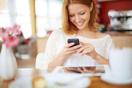 cafe internet: Imagen de la joven sms lectura femenina en el teléfono en el café