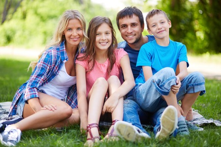 brothers and sisters: Photo of happy family of four spending time in park in summer Stock Photo