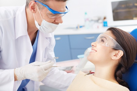 protective spectacles: Young happy girl looking at the dentist during oral checkup Stock Photo
