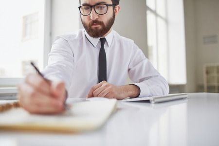 busy beard: Serious businessman sitting in office and working